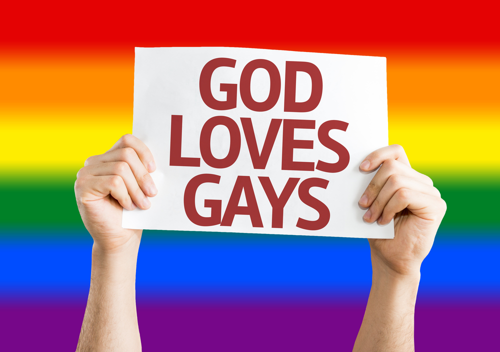 """A person holding up a sign that reads, """"God loves gays."""" There is a rainbow in the background."""