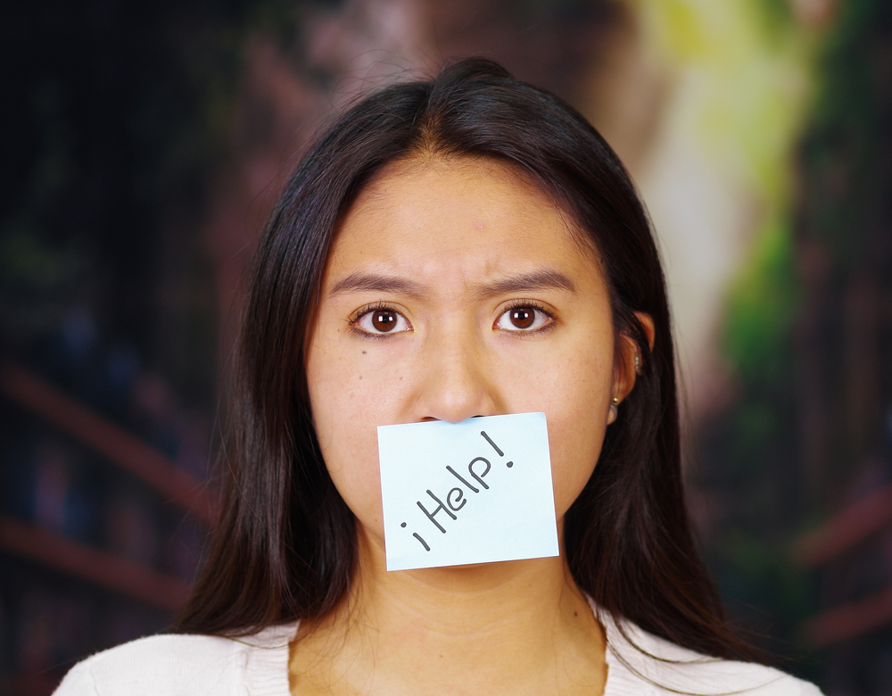 "A photo of a woman with a sticky note over her mouth that reads, ""help!"""