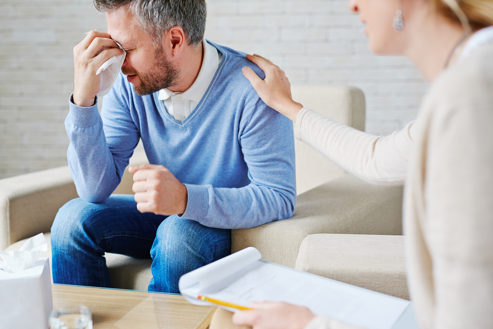 A man crying. A female psychiatrist has her hand on his shoulder.