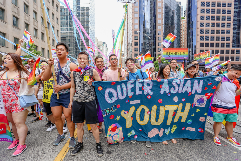 """A group of LGBT activists march through the streets with a sign that reads, """"Queer Asian youth."""""""