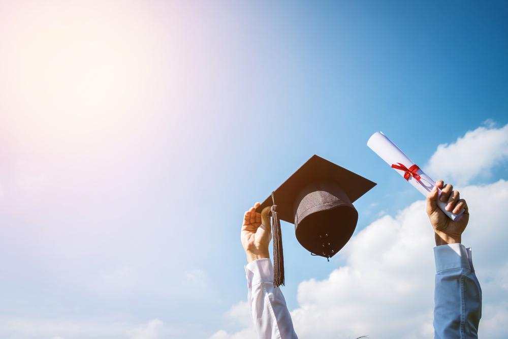 A high school graduate raises his cap and diploma in celebration.