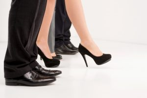A businesswoman steps forward in a line of businessmen, signifying female leadership.
