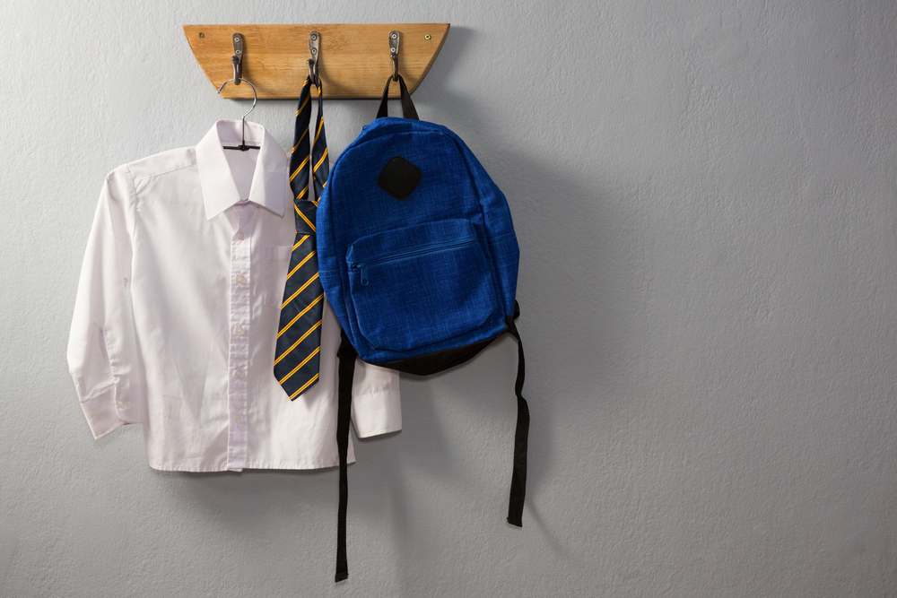 A backpack, a tie, and a white button-down top hanging from a set of hooks.