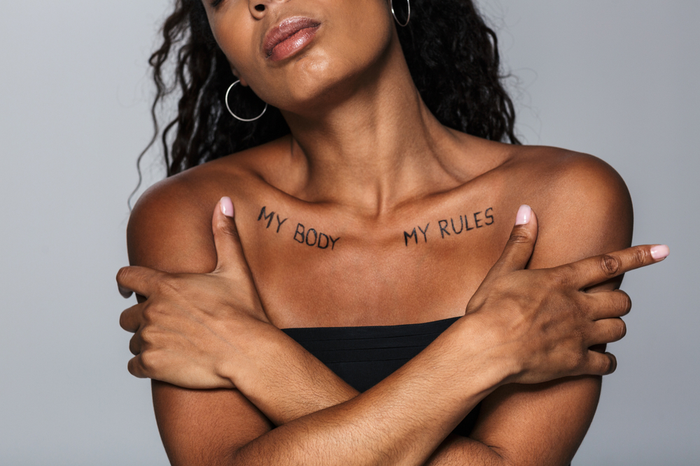"""A black woman with the words """"my body, my rules"""" written across her chest."""