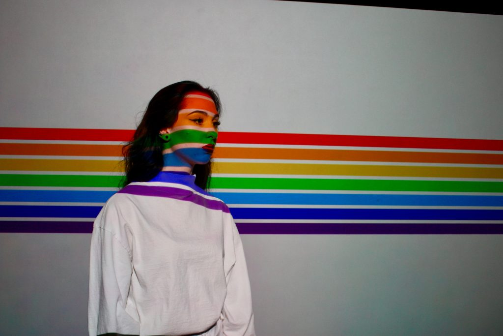 rainbow stripes painted on a wall and across a woman's face